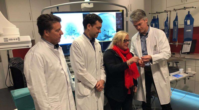Dr. Hannes Nordmeyer (v.r.) zeigt Andrea Kutscha im Beisein von Prof. Dr. Marcel Dihné und Dr. Ralf Buhl einen Draht, wie er bei der OP verwendet wurde.