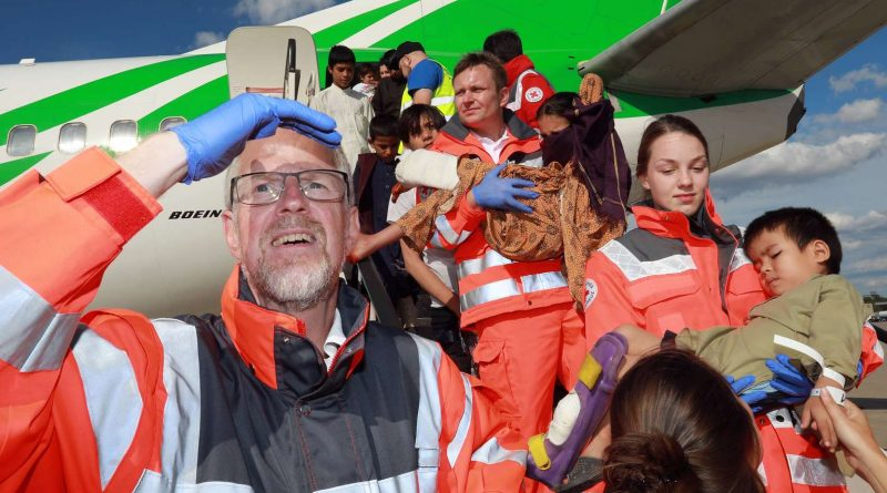 Am Heck der tadschikischen Boeing 737 koordiniert der Solinger DRK-Helfer Holger Migdalek (vorne) die Verteilung von 95 Kindern auf die Krankentransportwagen. Das Solinger DRK unterstützt seit 2007 das Oberhausener Friedensdorf auf Einsätzen.